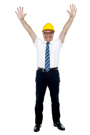 formals: Contemporary construction engineer celebrating success by throwing his hands up in the air. Stock Photo
