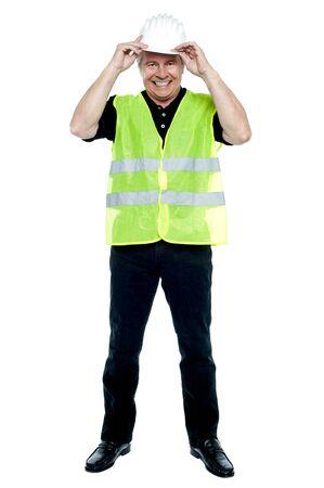 Construction worker in fluorescent jacket adjusting his safety helmet. photo