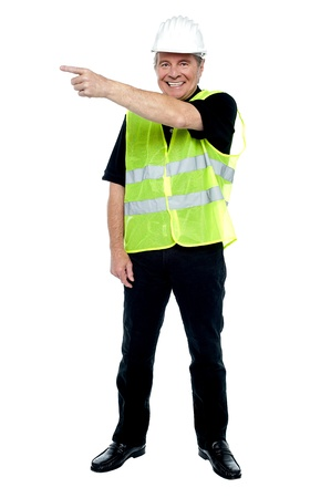Cheerful estate engineer indicating sideways. Copy space concept. Stock Photo - 17039057
