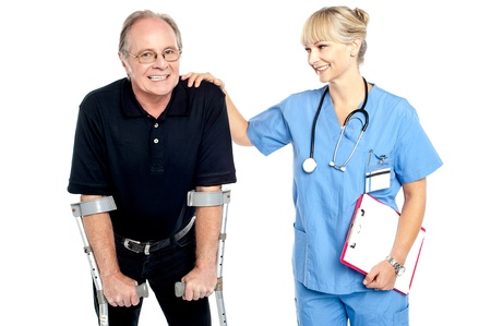 Cheerful doctor encouraging her patient to walk with crutches, smiling faces. Stock Photo - 17044555