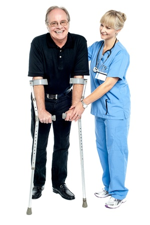 walker: Experienced physician assisting her patient in recovery process. Isolated on white. Stock Photo