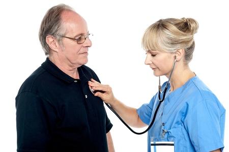 Female doctor examining an elderly man isolated against white background. Stock Photo - 17044667