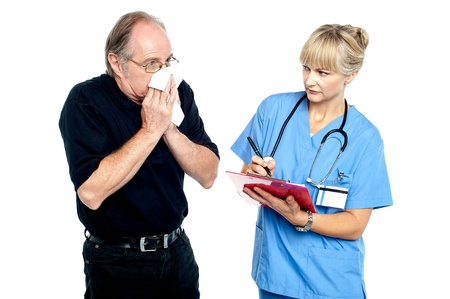 Aged male suffering from cold, sneezing. Female doctor looking at him. photo