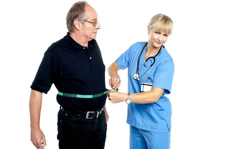Pretty female doctor measuring waist of senior surprised man. photo