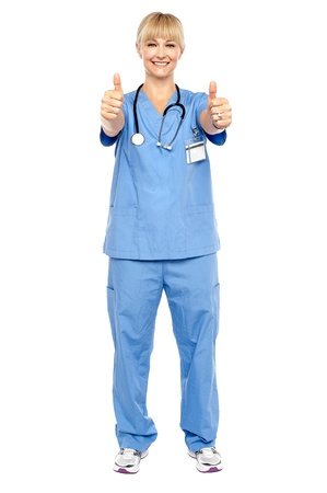 Cheerful lady doctor showing double thumbs up to the camera. Full length shot on white background. Stock Photo - 17044138