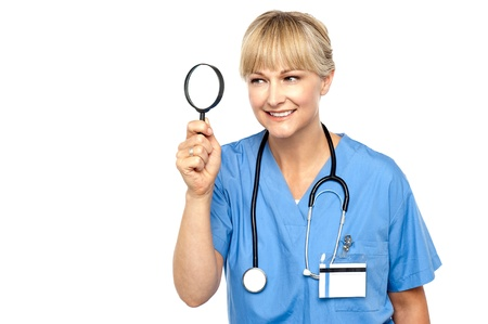 Pretty physician looking through magnifying glass, observing something closely. Stock Photo - 17044433