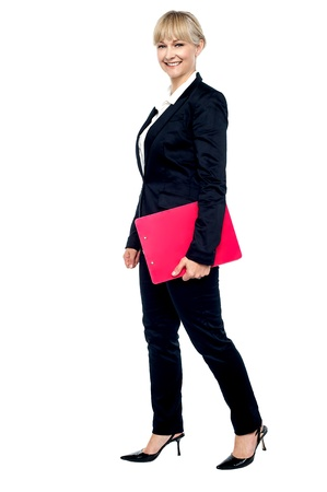 Energetic employee walking with her clipboard. Full length studio shot. Stock Photo - 17044042
