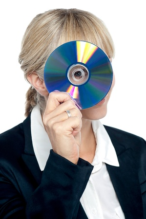 Young corporate lady looking at you through compact disc hole and smiling. photo