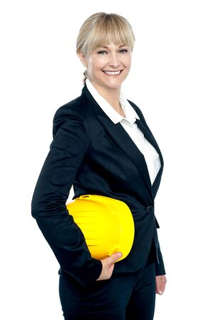 Pretty business architect with yellow safety helmet in hand, standing sideways and smiling. photo