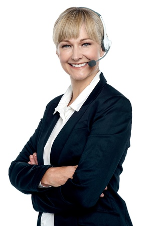 Cheerful female telecaller wearing headset and posing confidently with folded arms. photo