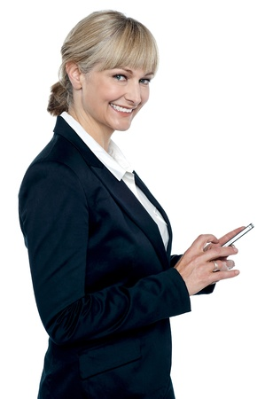 Female executive operating touch screen cellphone while smiling at camera. photo