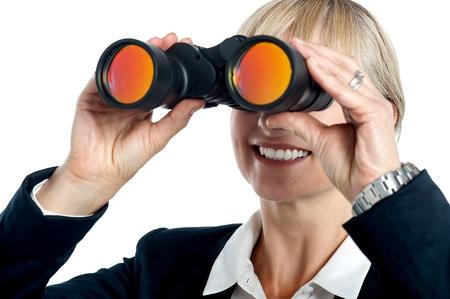Happy blonde corporate woman tracking far far away success through binoculars. Stock Photo - 17044599