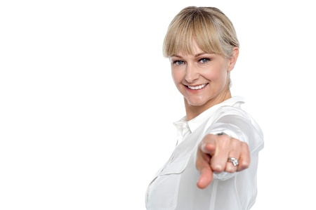 Stylish corporate woman standing sideways and pointing at you. All on white background. photo