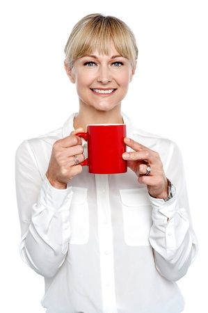 Female manager posing with coffee mug in hand. Studio shot photo