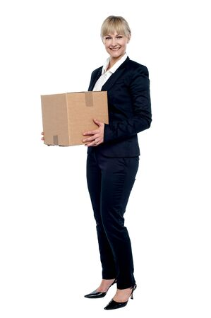 Female business executive relocating her office, carrying cardboard box. photo