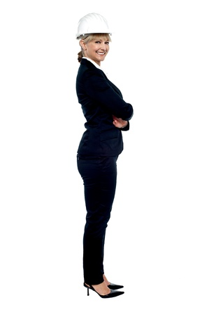 Female business architect posing sideways, arms crossed. photo