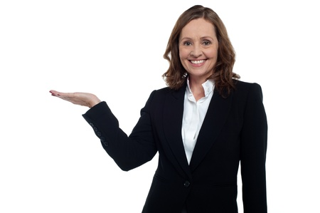 Middle aged corporate woman showing copy space to the camera, smiling warmly. Stock Photo - 17203797