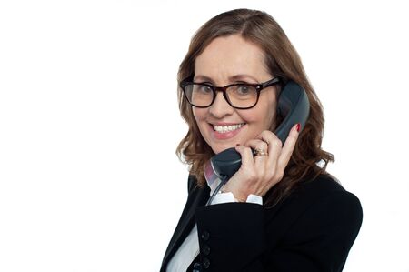 Bespectacled woman talking over the phone, business concept. Stock Photo - 17203822