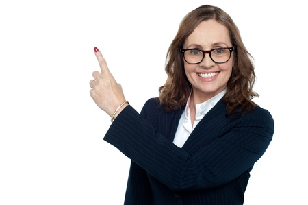 Beautiful executive in suit gesturing copy space, smiling warmly Stock Photo - 17204290