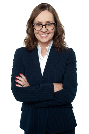 formals: Portrait of a confident businesswoman posing with folded arms over white background.