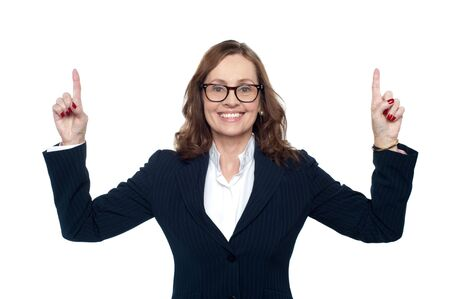 Cheerful corporate woman pointing upwards with both her hands. Stock Photo - 17203840