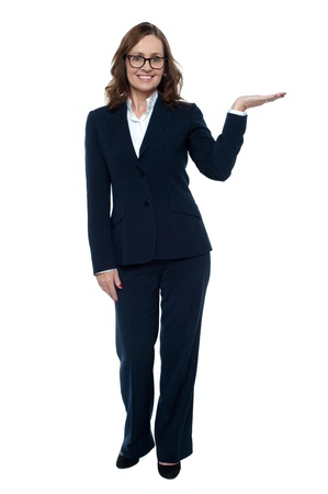 Woman in business attire posing with an open palm, copy space concept. photo