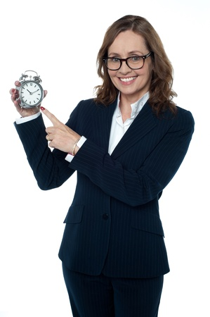 Corporate executive pointing towards the clock. Its 10:10 photo