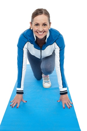 Cheerful woman doing yoga while she poses like a runner just before the race. Indoor shot Stock Photo