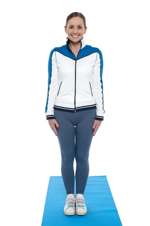 Active female posing just before her workout session, wearing track suit and standing on blue mat. photo