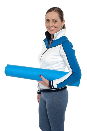 Woman carrying blue yoga mat. She is done for the day. Stock Photo - 17204343
