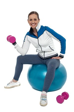 Fit woman doing biceps exercise with pink dumbbells. Sitting on big blue exercise ball. Stock Photo - 17204321