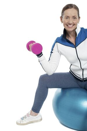 Cheerful woman seated on pilates and exercising with dumbbells. Stock Photo - 17204432