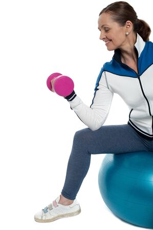 Woman on swiss ball working out with dumbbells, cropped image. Stock Photo - 17204403