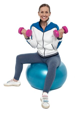 Middle aged fit woman exercising while sitting on a fitness ball with dumbbells. Stock Photo - 17204342