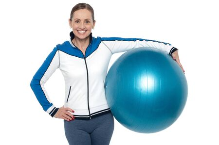Pretty woman holding big blue pilate ball against her waist and smiling. Stock Photo - 17204513