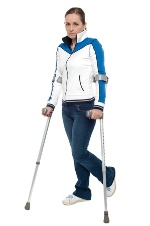 Pensive looking woman using crutches to walk, studio shot. photo