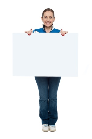 Portrait of a woman displaying a blank board to the camera, full length on white. photo