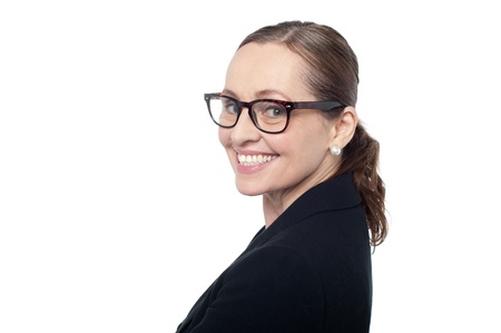 Side profile of a woman wearing spectacles smiling at the camera. photo
