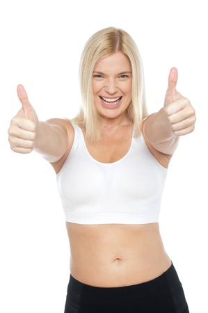 Fit woman in sports bra gesturing double thumbs up, extremely happy. Stock Photo - 17204301