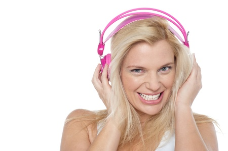 Hot blonde listening to music via headphones isolated against white background. photo