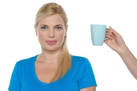 offered: Woman is being offered a cup of beverage, probably coffee.