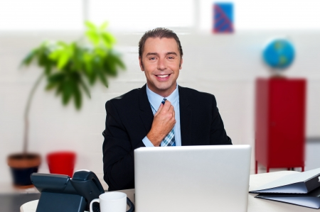 Happy boss at his new workstation adjusting his tie before business meeting. Stock Photo - 17204229
