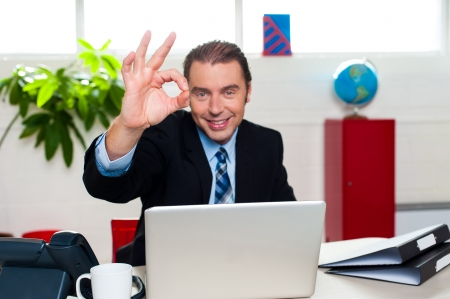 Cheerful male boss gesturing perfect sign while seated at his workstation. Stock Photo - 17204266