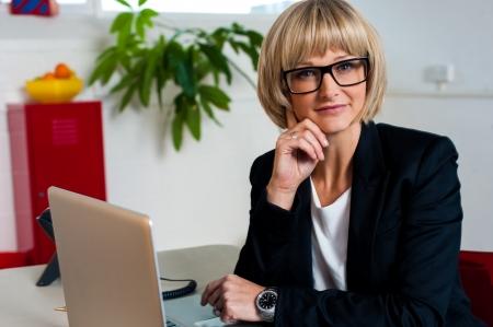 eye wear: Business lady wearing eye wear and facing camera. Indoor office shot. Stock Photo