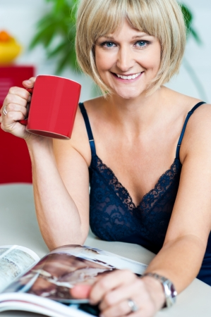 Good Morning. Pretty woman with a coffee mug in hand reading magazine early in the day. photo