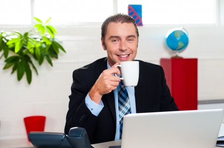 Boss at his workstation posing with coffee mug and laptop open in front of him. photo