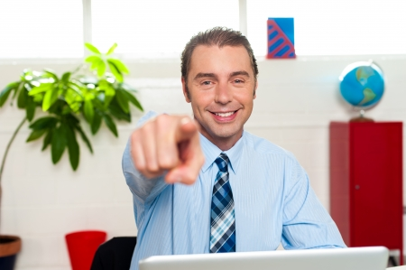 You, yes you! Great job done. Manager seated at his workstation pointing at you. Stock Photo - 17204285