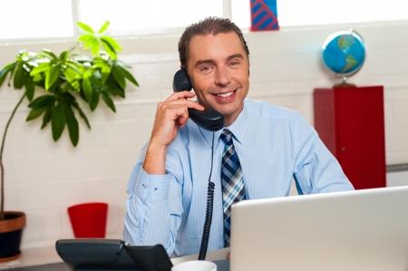 interakcje: Manager UÅ›miechniÄ™ta zaangażowany w interakcji biznesowych ponad rozmowy telefonicznej. Zdjęcie Seryjne