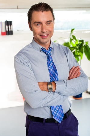 formals: Young male executive in formals standing with arms crossed. New office, indoors. Stock Photo