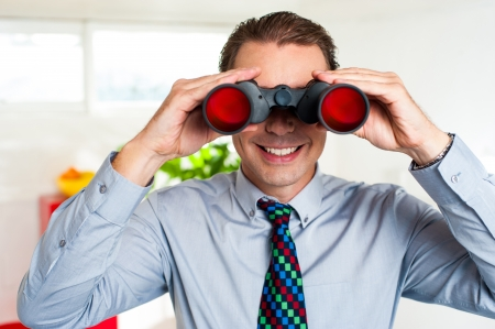Middle aged business executive tracking business success via binoculars. photo